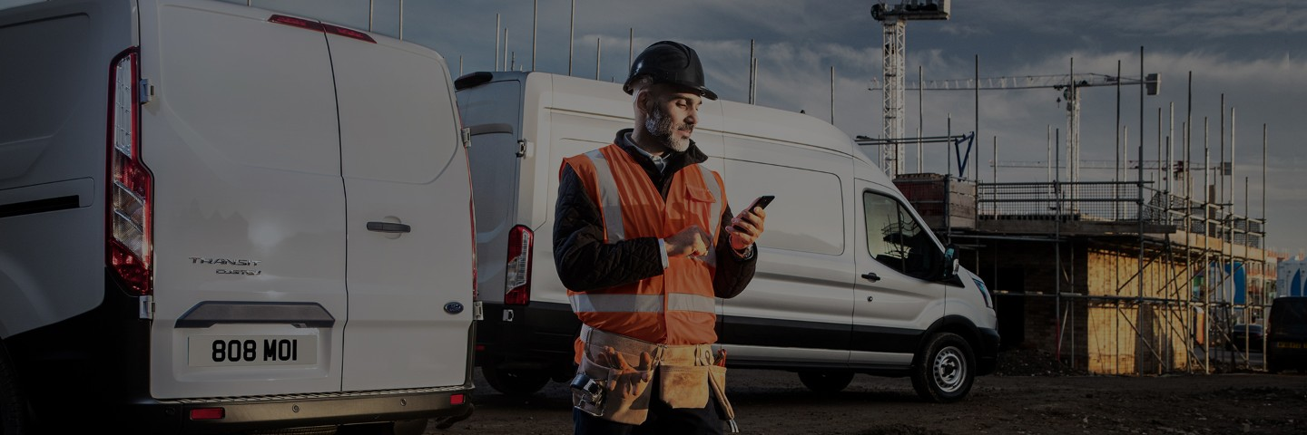 Service person with high viz jacket checking the FordPass Pro app